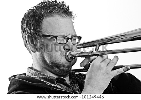 Musician - This is a high contrast black and white image of a you man playing a trombone. Shot on a white background and processed to enhance texture.