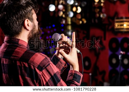 Musician with beard singing song in karaoke, rear view. Rock singer concept. Man in checkered shirt holds microphone, singing song, karaoke club background. Guy likes to sing in dark karaoke hall.