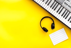 Musician work set with synthesizer, note  and headphones Yellow table background top view space for text