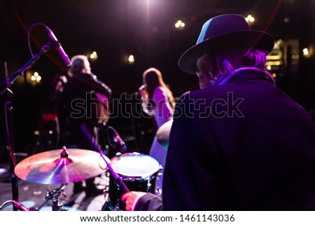 Musicians entertain people in night club. A back view of an elderly man playing drums on stage inside a nightclub, blurry band members are seen performing in the background with copy-space on the left