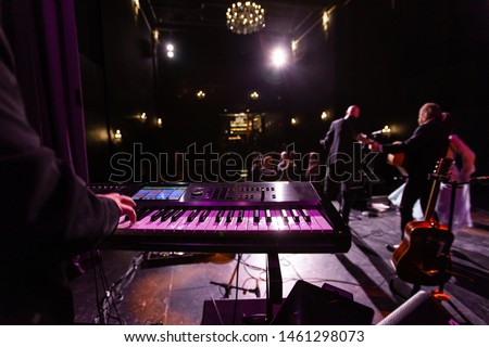 Musicians entertain people in night club. A closeup view on the hand of a keyboard player during a live music performance in a nightclub, blurry singers and guitar players are seen in the background.