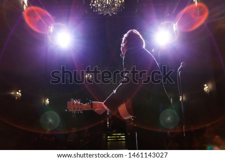 Musicians entertain people in night club. A low angle and back view of a guitarist performing a set on stage inside a nightclub, blurry spotlights are seen in the background with copy-space on the lef #1461143027