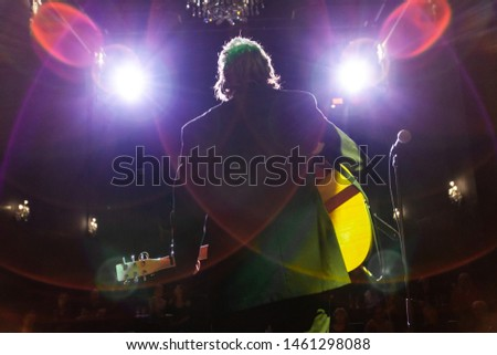 Musicians entertain people in night club. A low angle back lit view of a man playing a guitar by a mic stand in a music bar, bokeh stage lights are seen above as he plays to an audience.
