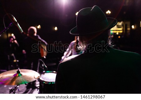 Musicians entertain people in night club. A rear view of a silhouetted man wearing a top hat as he performs a music gig on stage with fellow band members in the background and copy space on the left.