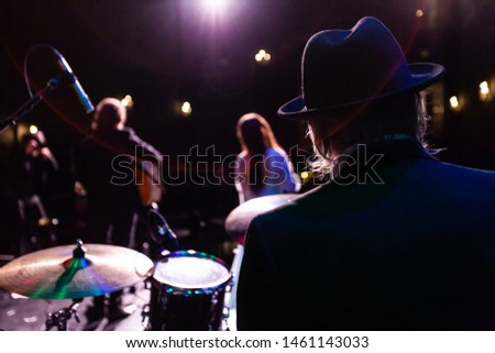 Musicians entertain people in night club. An over the shoulder view of a drummer sitting in front of a drum kit during a gig inside a music bar, a blurred singer and guitarist is seen in the backgroun