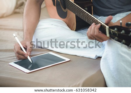 Musicians play guitar and compose songs using the tablet. #631058342
