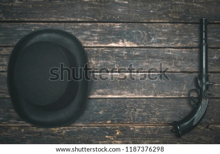 Musket gun, bowler hat on wooden table background. Duel.