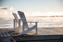 Muskoka chairs on a dock over looking lake Huron and Georgian Bay