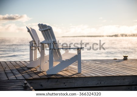 Muskoka chairs on a dock over looking lake Huron and Georgian Bay