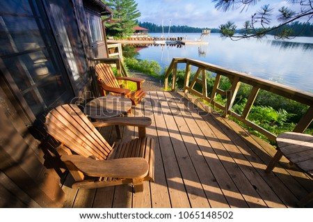 Muskoka chairs sitting on a wooden porch facing a calm lake. In the background there are Adirondack and Muskoka chairs on a wooden dock