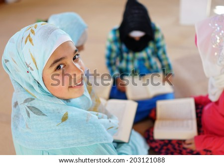 Muslim Arabic kids reading Koran at Mosque in Ramadan