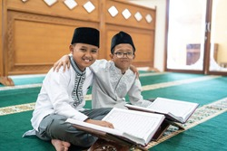 muslim asian kid bestfriend reading quran together at the mosque