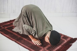 Muslim Boy  doing Salat with prostration pose on the prayer mat
