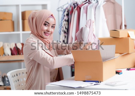 Muslim Business owner woman working online shopping prepare product packaging process at the office, young entrepreneur concept.