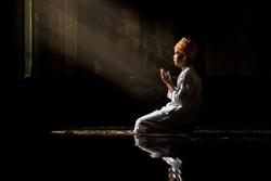 Muslim children kid men wearing white shirts Doing prayer reading book According to the principles of Islam.