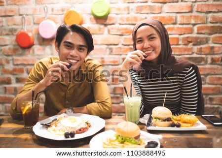 muslim couple breaking fast duing the month of ramadhan at cafe #1103888495