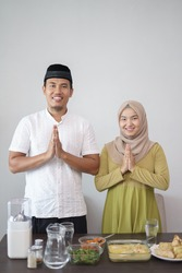 muslim couple greeting while standing in front of their table with food on hari raya eid mubarak kareem