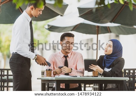 Muslim customer making her order at an outdoor cafee. Modern cafe start up small business micropayment concept. #1478934122
