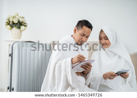 muslim family in white traditional clothes preparing luggage before hajj in Mecca