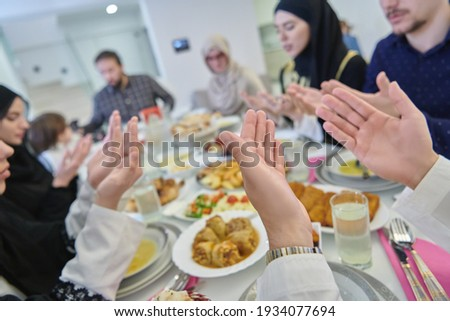 Muslim family making iftar dua to break fasting during Ramadan. Stok fotoğraf ©