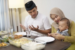 muslim family pray before having dinner together on ramadan