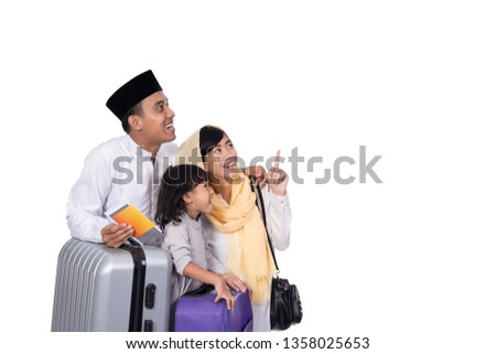muslim family with suitcase looking up to copyspace. ready for ramadan holiday