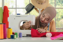 muslim fashion designer and dressmaker in hijab using sewing machine making her fashion clothing in fashion studio