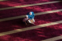 Muslim father and son praying together. Muslim dad and son praying in the mosque and reading holy koran inside the mosque.