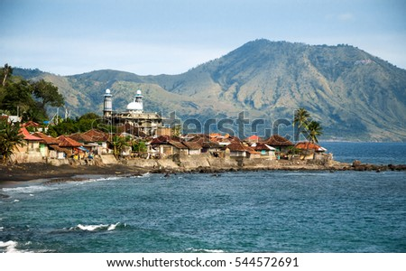 Shutterstock Muslim fisherman village with mosque and volcano at the background. Near Ende, Flores Island, Indonesia.