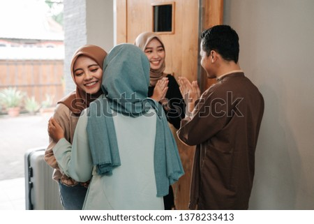 muslim friend and family visiting home and greet embrace each other celebrating eid mubarak #1378233413