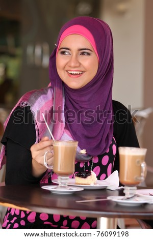 Muslim girl happy at the coffee table