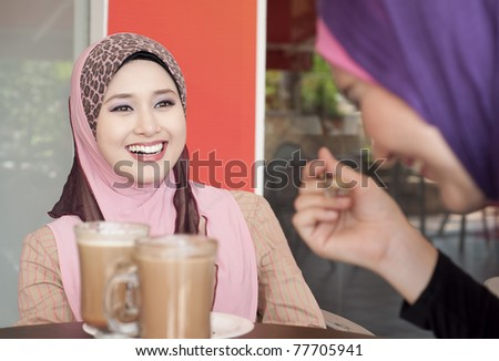 Muslim girl having fun with her friend at cafe