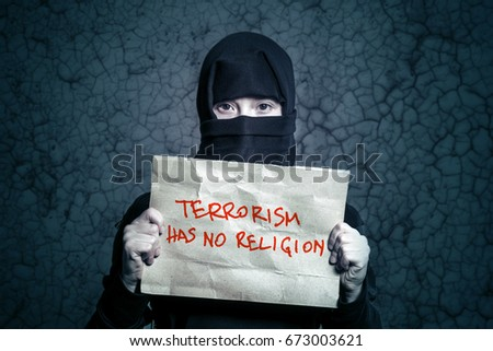 Muslim girl in black hijab holding a poster with an inscription TERRORISM HAS NO RELIGION on the background wall with cracks