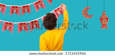 Muslim Kid preparing decorations to celebrate Ramadan festival - lantern , crescent , and paper Islamic shapes with word Ramadan Kareem - Translation : Ramadan is generous
