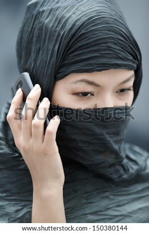 Muslim lady in hijab talking via cell phone