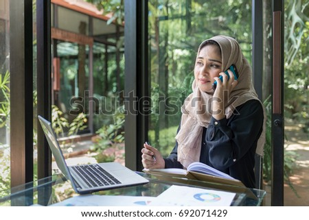 Muslim lady is busy on the phone at her desk.