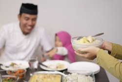muslim man breakfasting dinner with his daugther and family at home