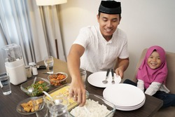 muslim man breaking the fast dinner with his daugther and family at home