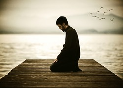 Muslim man fasting Ramadan and praying on beautiful lake (old look photo with noise added)