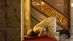 muslim man having worship and praying for allah blessing in islam ceremony in mosque during islamic ramadan period