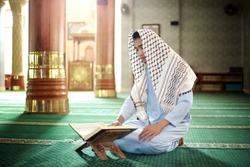 Muslim man reading koran in mosque