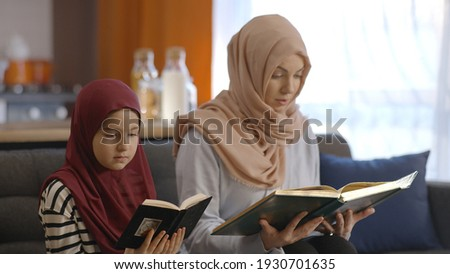 Muslim mother and daughter with a headscarf read the Quran together. Muslim mother and daughter sit next to each other at home and read the Quran. The Quran reading concept.