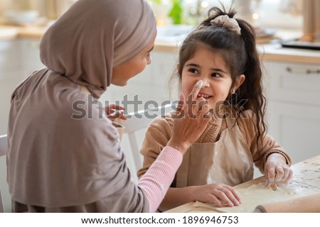 Muslim Mother And Her Little Child Having Fun While Cooking In Kitchen Together. Happy Islamic Family Fooling With Each Other While Baking At Home, Mom Playfully Touching Daughter's Nose, Closeup