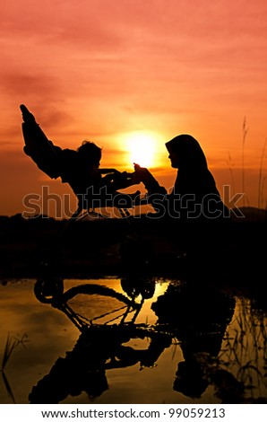 Muslim mother playing with her baby during sunset at park