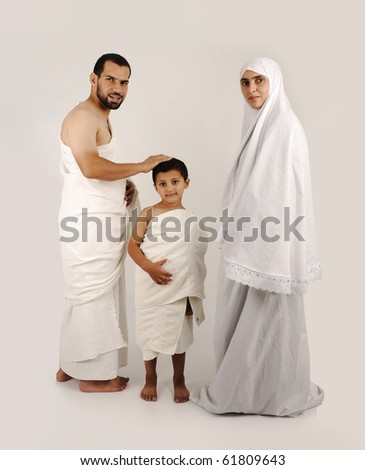 muslim pilgrims in white traditional clothes, family, woman, man and child (wife and husband and son)