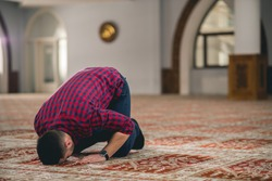Muslim praying, prostrating on the ground