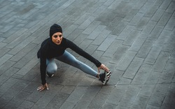 Muslim urban runner training in the city center. Beautiful woman doing sport in the early morning