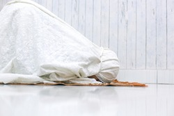Muslim woman doing Salat with prostration pose on the prayer mat