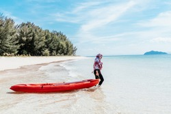 Muslim woman dragging her kayak to the water on the beach for watersports.  asian woman dragging ber boat around island. Travel concept. Summer time.