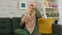 Muslim woman drinking with painkiller water. Portrait of muslim woman suffering from headache.